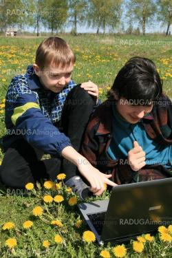 Two brothers with laptop computer on a colorful meadow