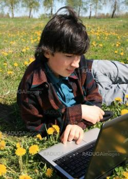 a young teenager on a green meadow with computer