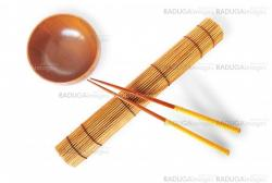 rolled bamboo mat with a pair of chopsticks  and wooden bowl