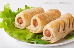 sausage in the dough on a plate with greens