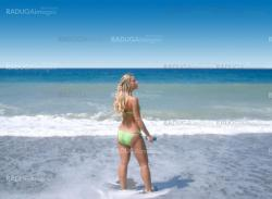 blond woman back at the seaside