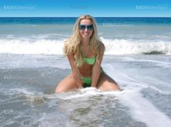 blond woman kneeling  in the surf on a beach