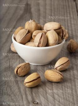roasted pistachios on a natural wooden background