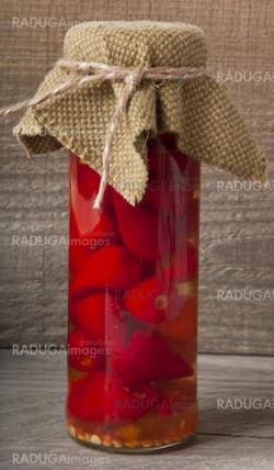 Red hot pepper in the pot on a wooden background