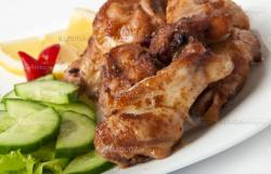 Grilled chicken on a white plate with vegetables on the background.