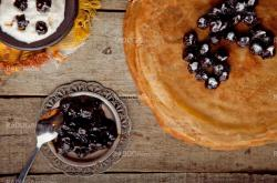 Crepes on the wooden table with cherry